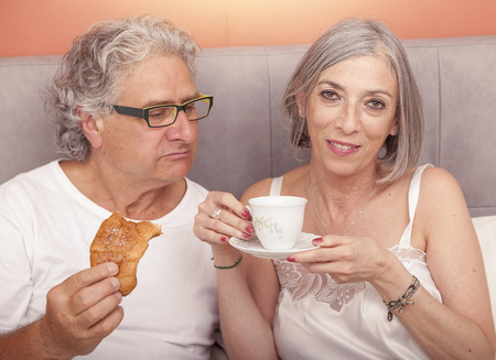 pretty mature couple having fun in the bed while eating breakfast