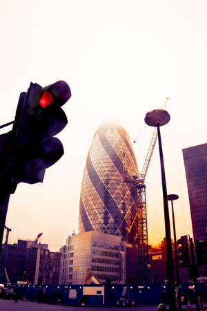 warm color: view of gherkin tower in London photographed from below a traffic light on a vintage warm color filtered look Stock Photo