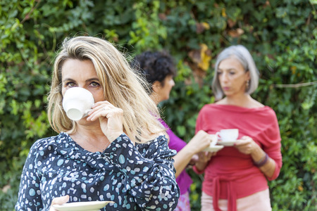 lady drinking a cup of tea with friends