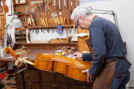 그의 실험실에서 바이올린을 테스트하는 동안 성숙한 바이올린 제작자의 초상화