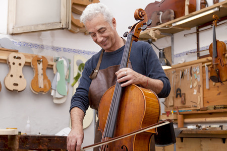 violin making: portrait of mature violin maker while testing the violins in his laboratory