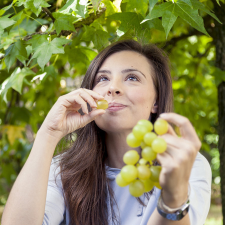 under a tree: young beautiful girl sitting under a tree eating grapes Stock Photo