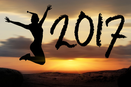to celebrate the New Year 2017 silhouette of young woman jumping on the beach Stock Photo