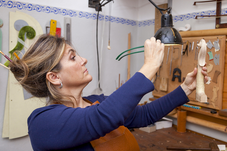 violin making: portrait of female mature violin maker while testing the violins in his laboratory
