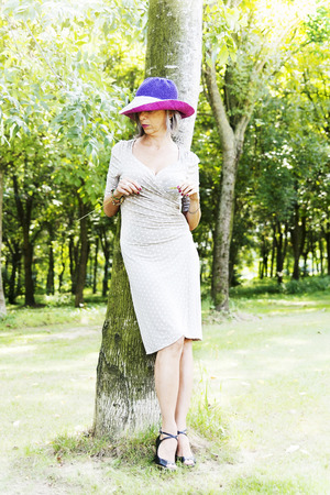 beautiful lady relaxing near a tree in the woods Stock Photo