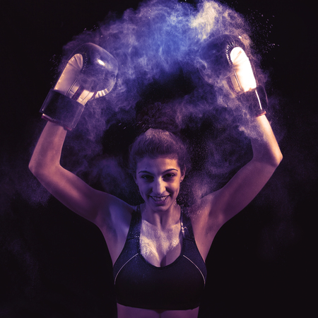 young boxer girl strikes up his gloves in the powder