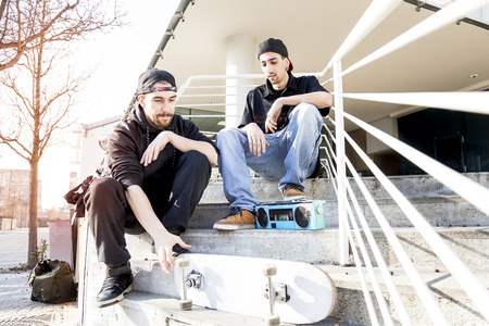 two young skateboarder relax on the outskirts stairs Stock Photo