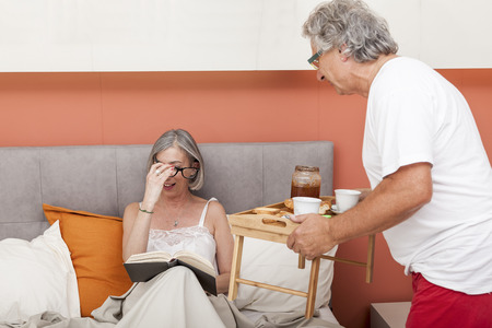 caring husband brings  breakfast in bed his wife Stock Photo