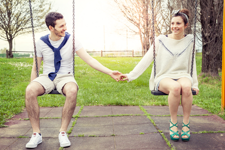 pair of young lovers hand in hand on the swing outdoor in the park Stock Photo
