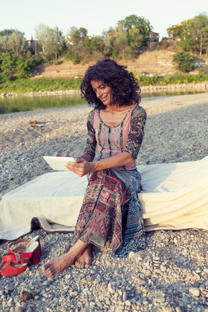 arpa: portrait of beautiful harpist woman typing messages on the tablet at sunset by the river bank Foto de archivo