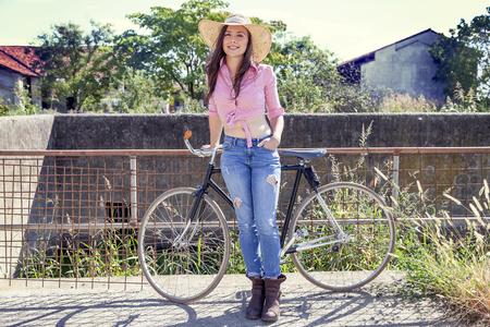 Hübsche junge Frau auf dem Fahrrad in einer Landstraße Standard-Bild - 79648939