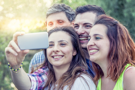snapshots: Happy group of young people takes a selfie outdoor in the summertime Stock Photo