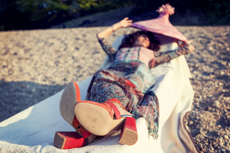 beside: Beautiful woman plays with her straw hat beside a river Stock Photo