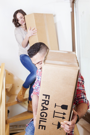 young couple carrying the boxes in new house Stock Photo