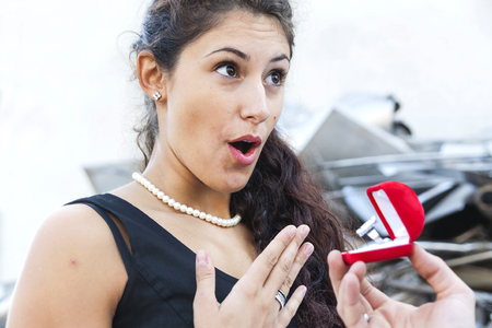 pretty woman receives a ring as a gift in a junkyard very strange location