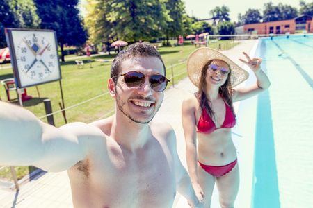 Young loving couple beside the pool takes a selfie in swimsuit. Concept of young people having fun in summertime Reklamní fotografie - 81623915