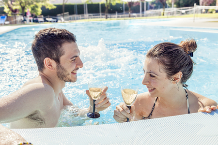 Young loving couple relaxes and drink wine in the hydromassage of swimming pool. Concept of young people having fun in summertime