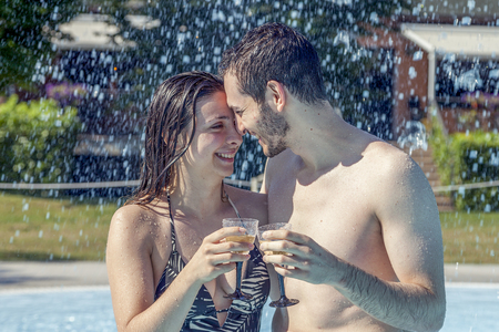 Young loving couple kisses and drink wine in the hydromassage of swimming pool. Concept of young people having fun in summertime Stock Photo