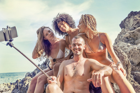 brazilian ethnicity: Group of happy people take a selfie on a rock in the middle of the sea.  Concept of beautiful people having fun in summertime Stock Photo