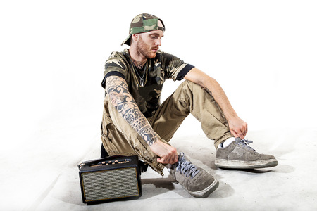 sitting tattooed rap singer posing in studio with an amplified radio on a white background