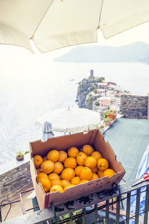 oranges in a box exposed outdoors in front of a sea view