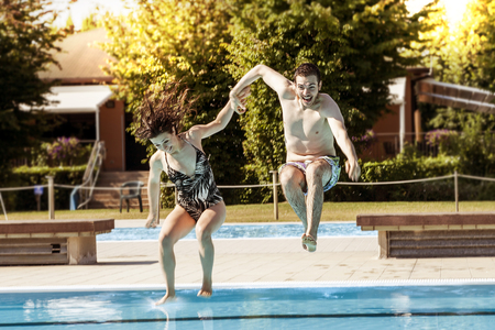 young couple of lovers jumping in the swimming pool. Concept of beautiful people having fun in summertime