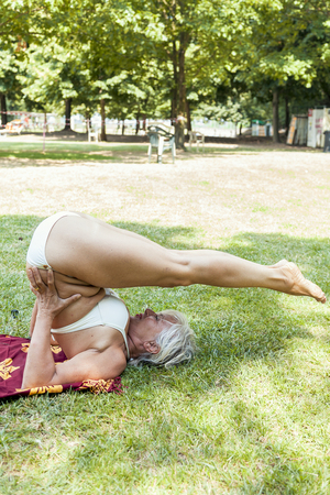 mature woman in bikini does handstands in a public park. Concept of beautiful people having fun in summertime