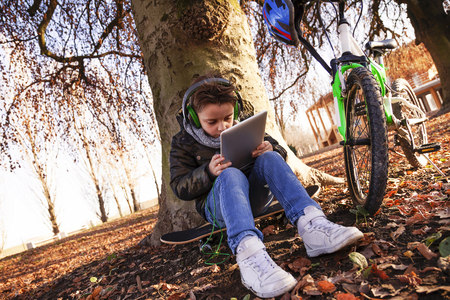 Elegant child plays with a tablet pc sitting among the leaves in winter outdoors