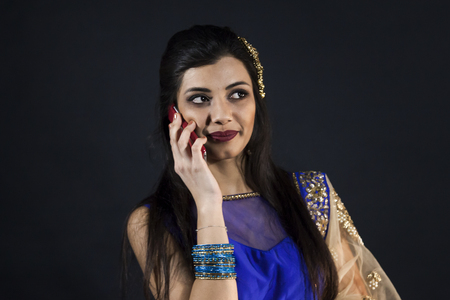 smiling beautiful indian girl calling with smart phone. young female model wears jewelry sets and traditional blue clothes