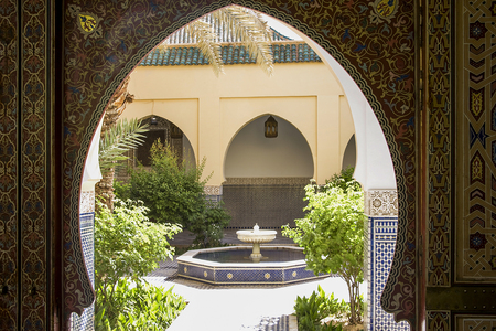 patio with fountain in modern Arab palace with arabesques on arched door