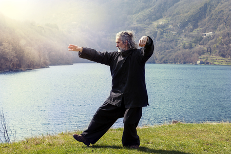 mature man practicing Tai Chi discipline outdoors in a lake park on a winter day