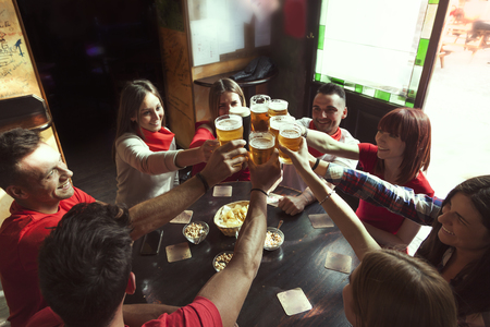 group of people celebrating in a pub drinking beer and eating snacks Stock Photo