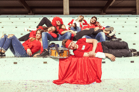 young group of supporter fans dressed in red color relaxing lying down in the stands after the match Stock Photo