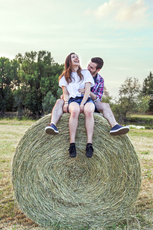 Couple of lovers having fun outdoors on a summer sunset sitting on a sheaf of hay