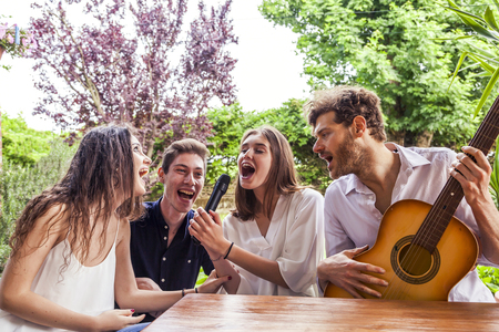 group of young friends having fun singing a song in the courtyard of a country house