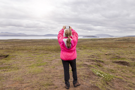 attractive mature woman taking a photo with the smart phone in the lands with Icelandic moss