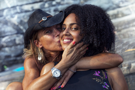 couple of beautiful women of different ethnicity while hugging on beach vacation