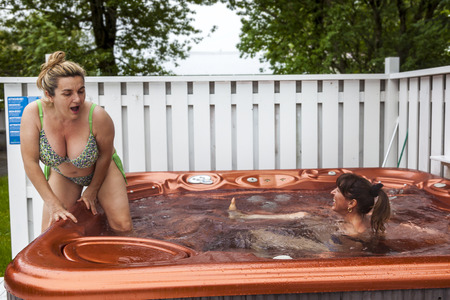 couple of ladies on vacations having fun and enjoying the benefits of the outdoor hot tub while it rains