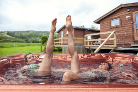 couple of ladies on vacations having fun and enjoying the benefits of the outdoor hot tub. Icelandic guest house on background