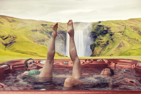couple of ladies on vacations having fun and enjoying the benefits of the outdoor hot tub. Icelandic Skogafoss waterfall on background