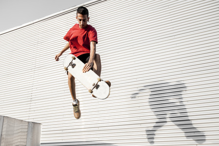 young skateboarder jumps up with his board in front of a metal background on the roofs of an abandoned building Foto de archivo - 111362118