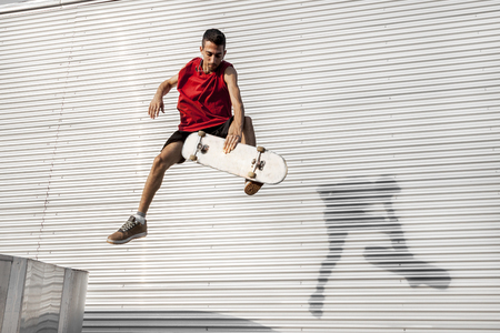 young skateboarder jumps up with his board in front of a metal background on the roofs of an abandoned building
