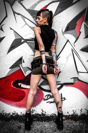 Fille rebelle tatouée contre un mur peint avec des graffitis menottés derrière le dos