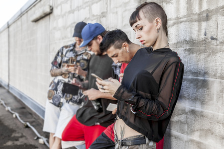 group of tattooed friends using smart phone against a gray wall over a roof - Young people addicted by mobile smartphone - Technology millennials concept