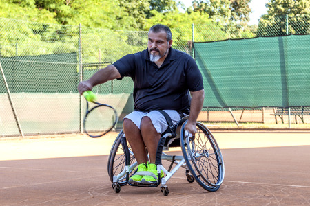 disabled tennis player hits the ball backhand during a match outdoor Foto de archivo
