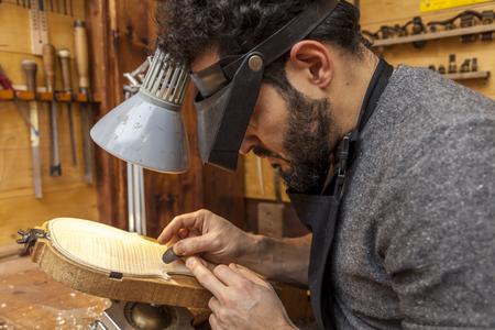 craftsman violinmaker began working on a new violin in his workshop 免版税图像