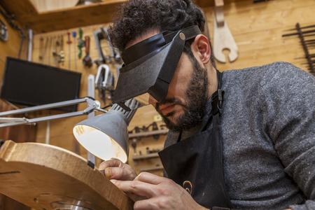 craftsman violinmaker began working on a new violin in his workshop