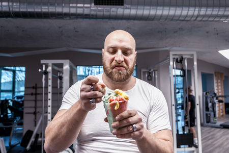 portrait of athlete while eating an ice cream on break after training in the gym Foto de archivo