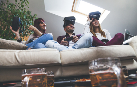 Young happy three friends playing video games virtual reality glasses in their apartment - concept of cheerful people having fun with new trends technology