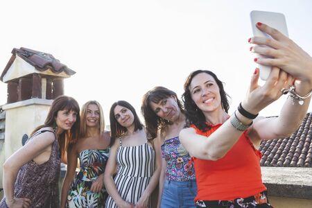 Grupo de amigas tomando un selfie con smarthphone - gente divirtiéndose con la tendencia de las nuevas tecnologías - Concepto de amistad con chicas compartiendo el momento en las redes sociales Foto de archivo